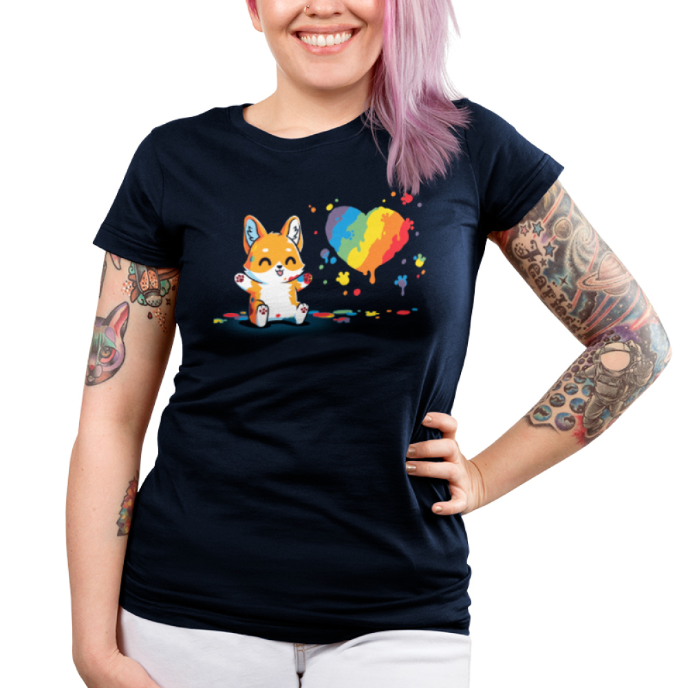 Paw Painting (Corgi) Junior's t-shirt model TeeTurtle navy t-shirt featuring a corgi sitting up covered in multiple paint colors beside a rainbow heart with colorful pawprints and splatters all around.