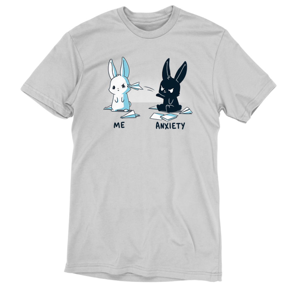 Me vs. Anxiety silver t-shirt featuring a mischievous black bunny sitting down throwing a paper airplane at an annoyed white bunny with paper airplanes and paper scattered on the ground.