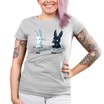 Me vs. Anxiety Junior's t-shirt model TeeTurtle silver t-shirt featuring a mischievous black bunny sitting down throwing a paper airplane at an annoyed white bunny with paper airplanes and paper scattered on the ground.