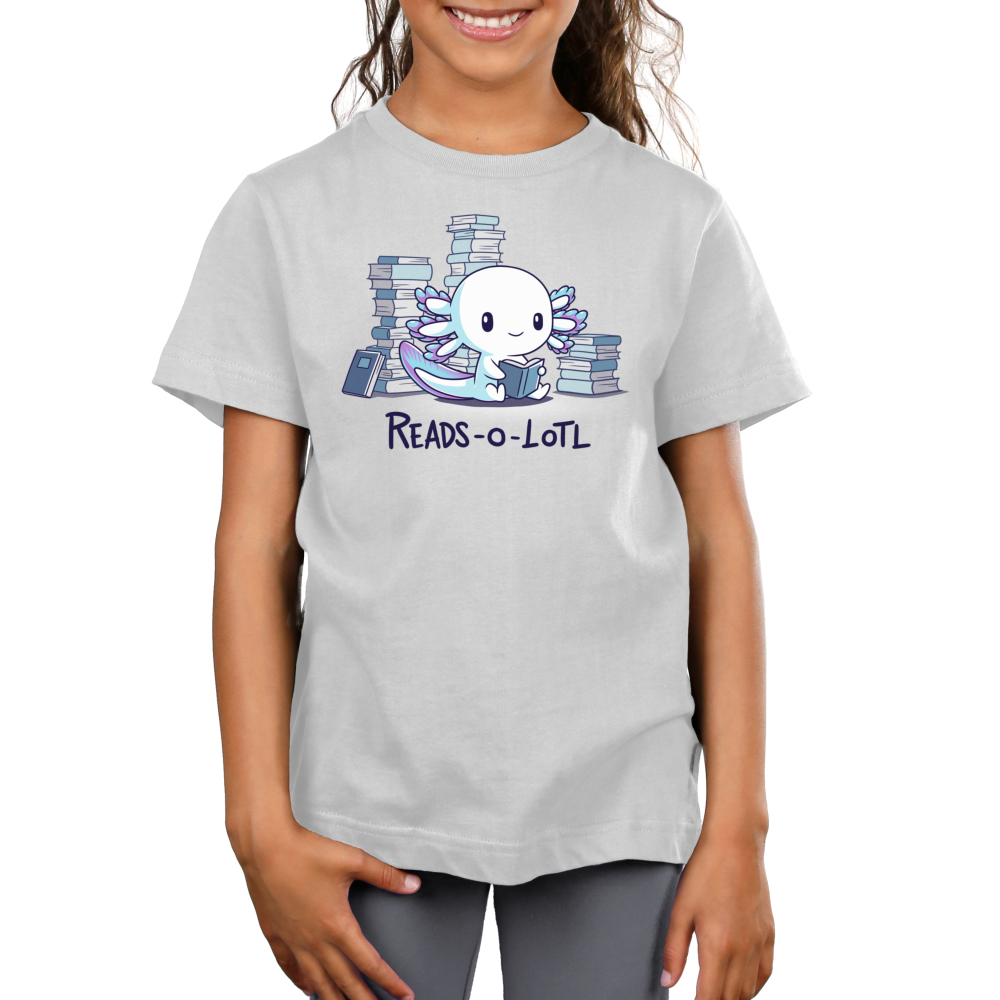 Reads-o-lotl Kid's t-shirt model TeeTurtle silver t-shirt featuring a happy white axolotl with purple and blue gills sitting down while reading a book with stacks of books in the background.