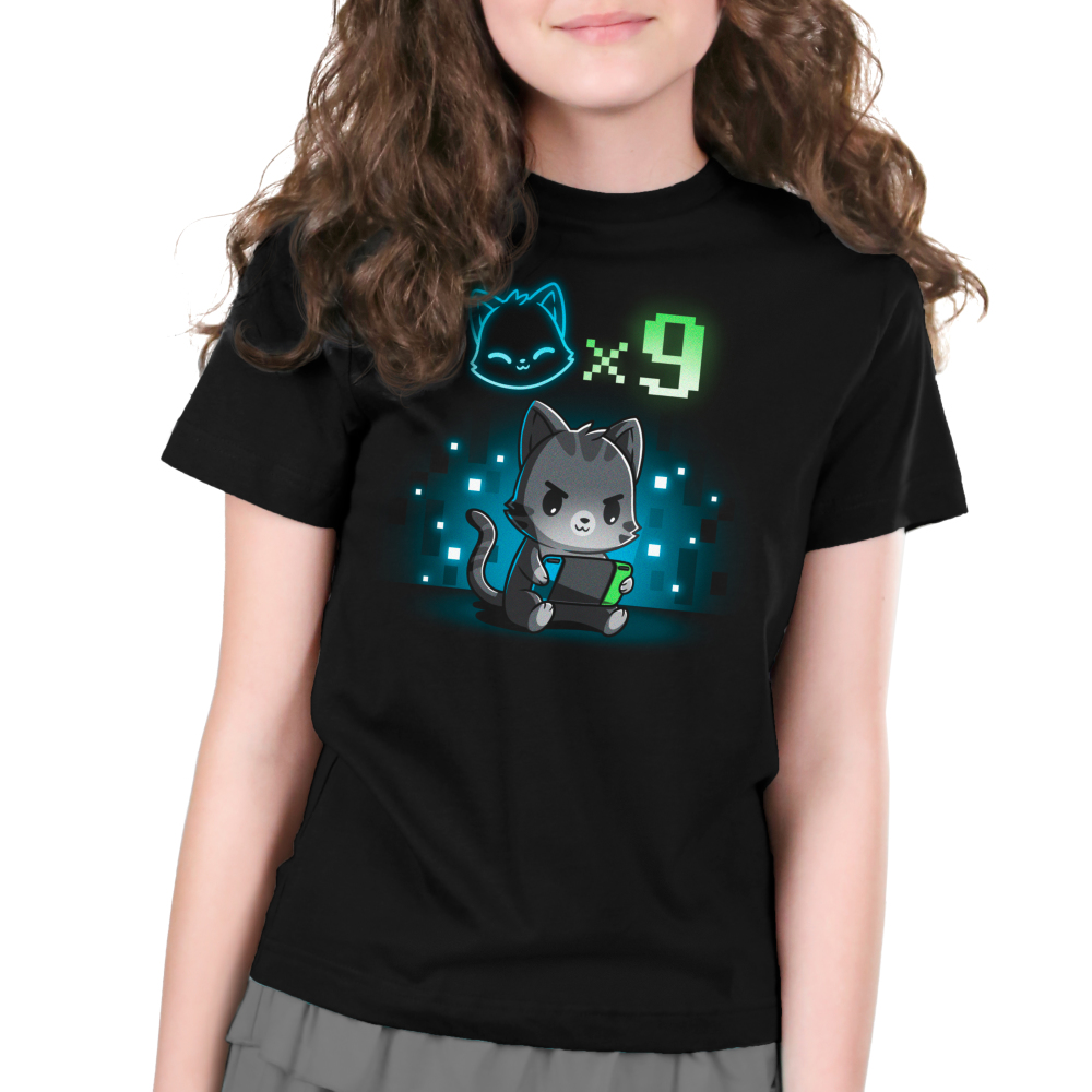 I Have Nine Lives Kid's t-shirt model TeeTurtle black t-shirt featuring a gray tabby cat sitting down and playing on a green, blue, and black video game console with a cat icon multipliedby nine above its head, and with a background of blue and white pixel-like wallpaper.