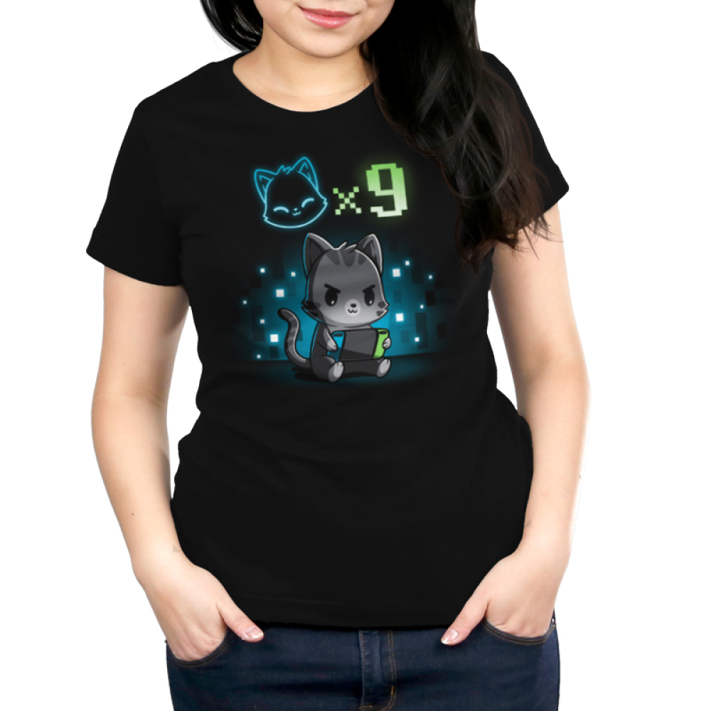 I Have Nine Lives Women's t-shirt model TeeTurtle black t-shirt featuring a gray tabby cat sitting down and playing on a green, blue, and black video game console with a cat icon multipliedby nine above its head, and with a background of blue and white pixel-like wallpaper.
