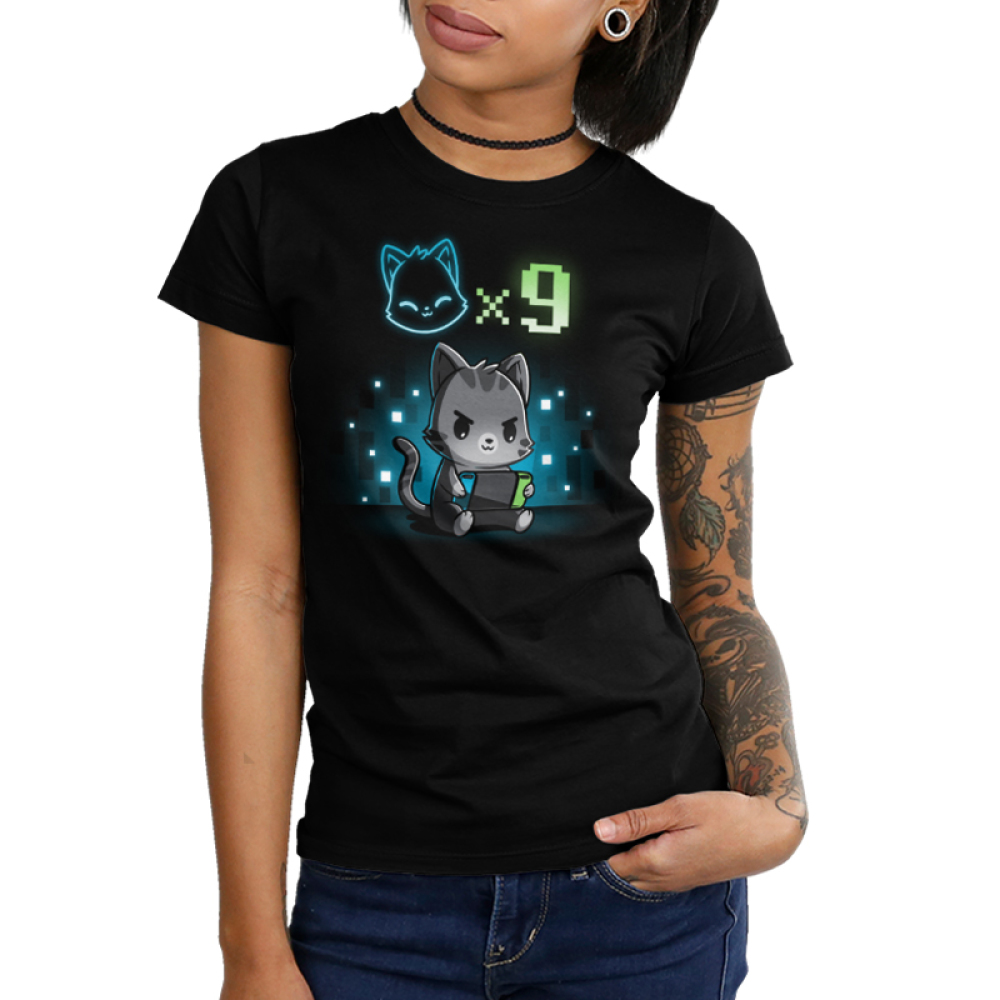 I Have Nine Lives Junior's t-shirt model TeeTurtle black t-shirt featuring a gray tabby cat sitting down and playing on a green, blue, and black video game console with a cat icon multipliedby nine above its head, and with a background of blue and white pixel-like wallpaper.