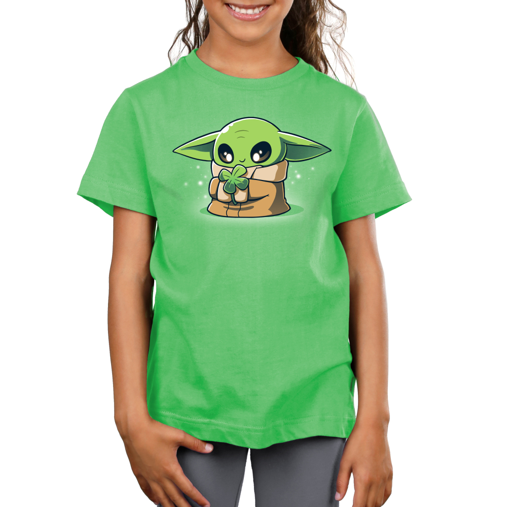 Lucky Grogu kid's t-shirt model officially licensed apple green Star Wars t-shirt featuring Grogu from the Mandalorian where he is smiling and holding a four leaf clover