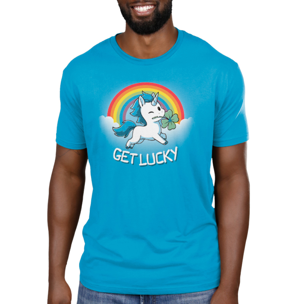 Get Lucky (Unicorn) Men's t-shirt model TeeTurtle cobalt blue t-shirt featuring a white unicorn with blue fur holding a clover in its mouth with clouds and a rainbow behind him