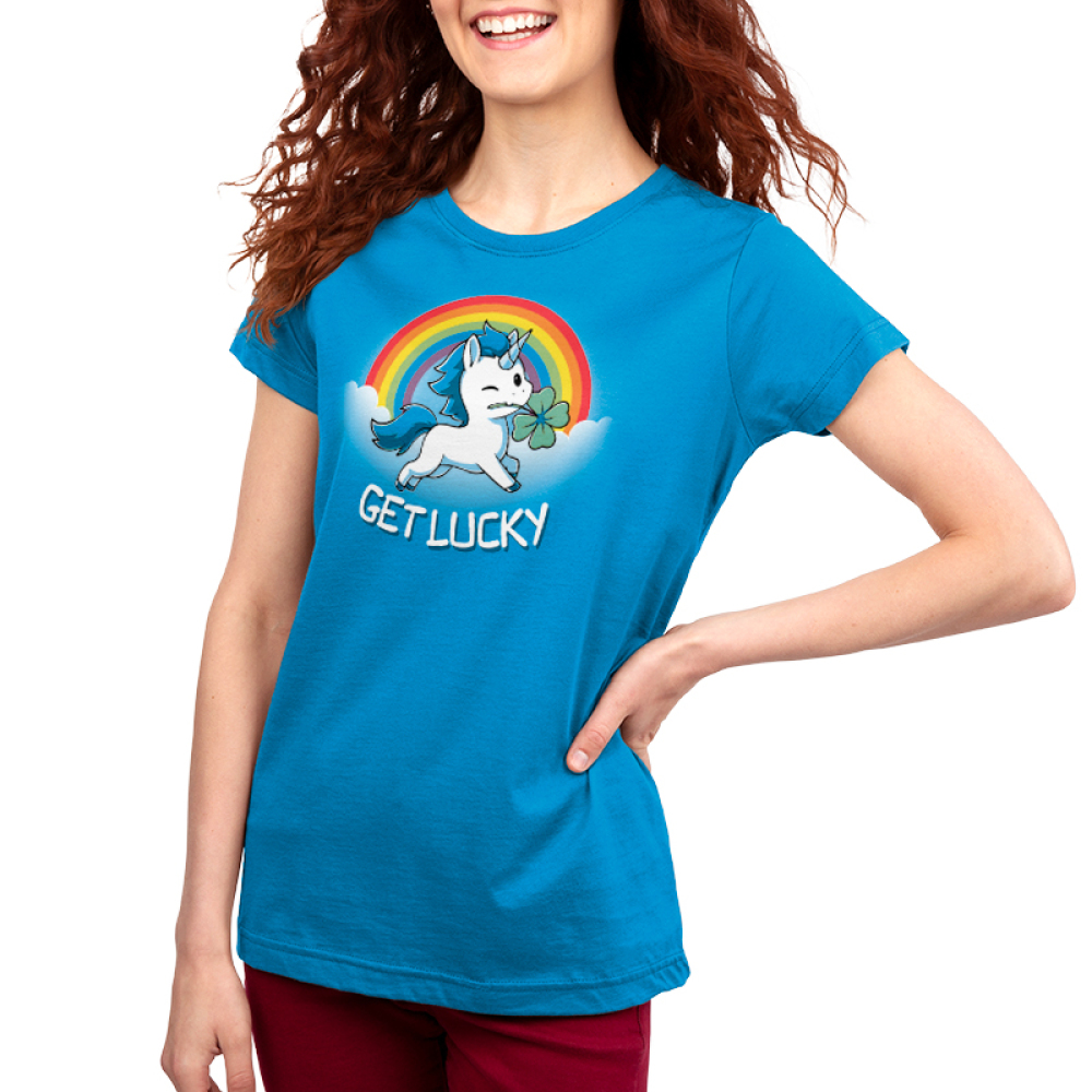 Get Lucky (Unicorn) Women's t-shirt model TeeTurtle cobalt blue t-shirt featuring a white unicorn with blue fur holding a clover in its mouth with clouds and a rainbow behind him