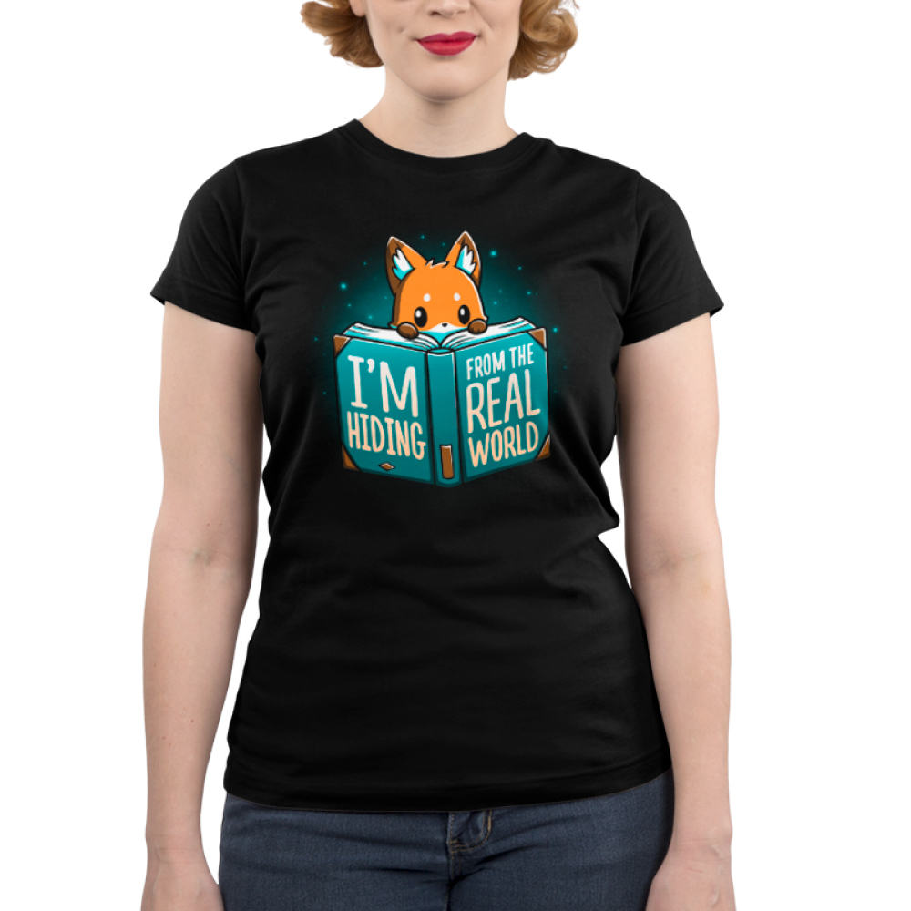 I'm Hiding From the Real World Junior's t-shirt model TeeTurtle black t-shirt featuring a fox crouching behind a big blue book with his paws and head peaking over the pages