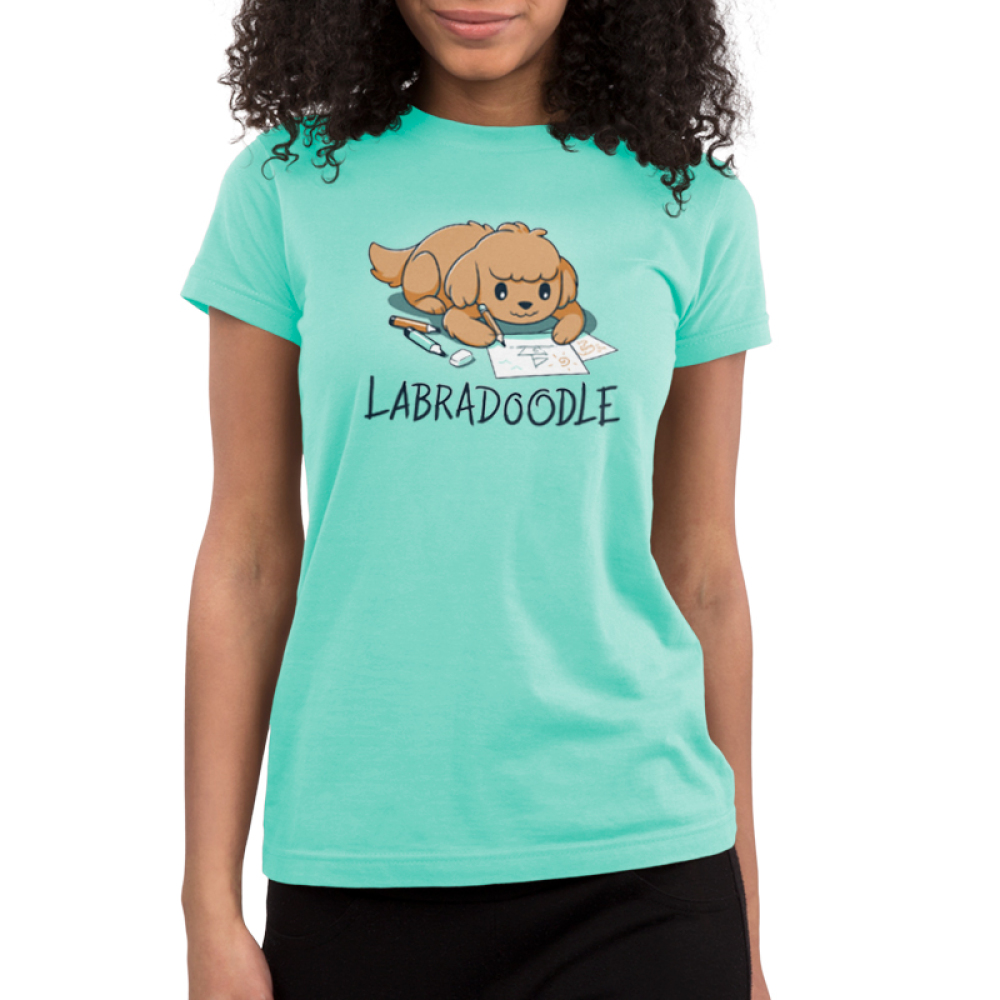 Labradoodle Junior's t-shirt model TeeTurtle chill blue t-shirt featuring a brown lab dog on the floor coloring pictures of boats with pencils and markers around him