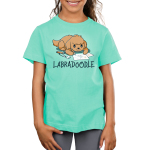 Labradoodle Kid's t-shirt model TeeTurtle chill blue t-shirt featuring a brown lab dog on the floor coloring pictures of boats with pencils and markers around him