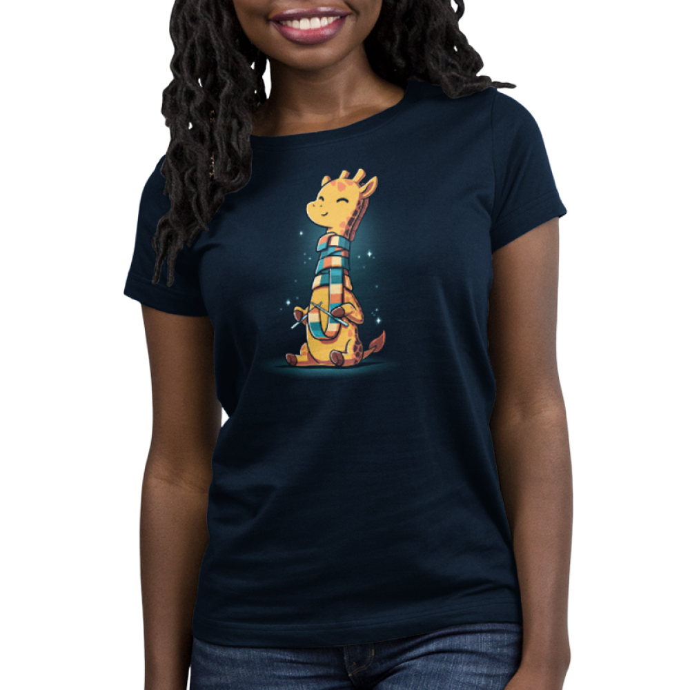 World's Longest Scarf Women's t-shirt model TeeTurtle navy t-shirt featuring a yellow and orange giraffe sitting down knitting a scarf as it wraps around its long neck