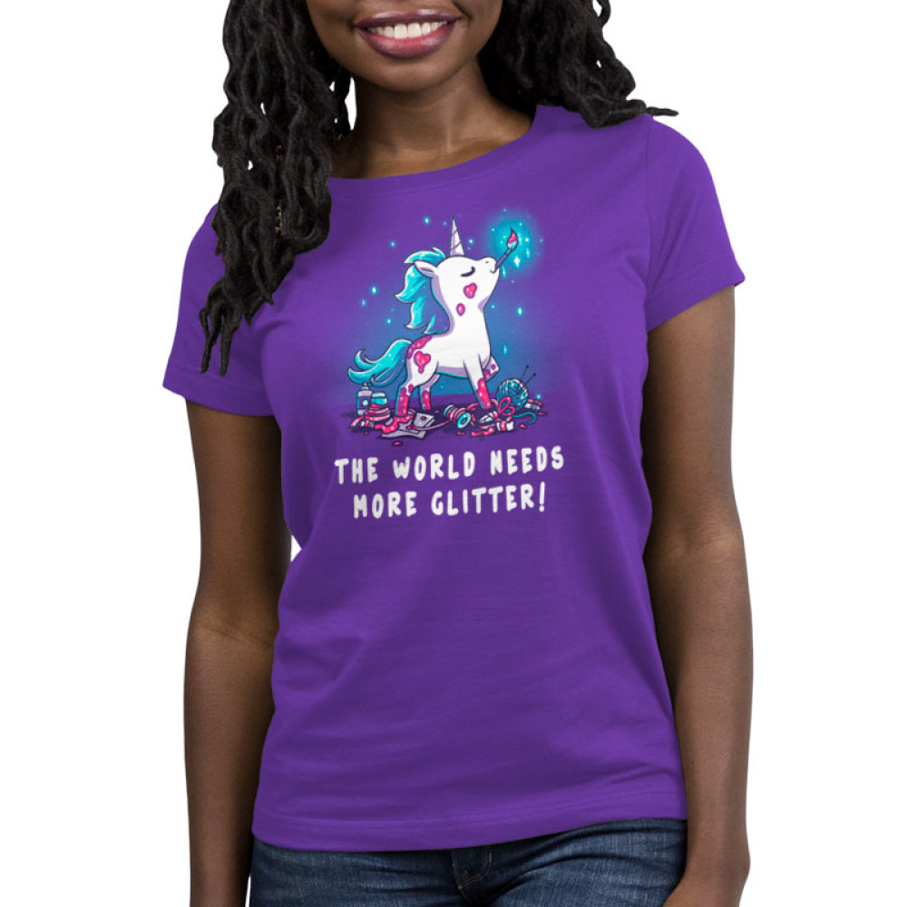The World Needs More Glitter Women's t-shirt model TeeTurtle purple t-shirt featuring a white unicorn with blue fur with pink glitter all over her holding a paint brush in her mouth and crafting supplies scattered by her feet
