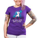 The World Needs More Glitter Junior's t-shirt model TeeTurtle purple t-shirt featuring a white unicorn with blue fur with pink glitter all over her holding a paint brush in her mouth and crafting supplies scattered by her feet