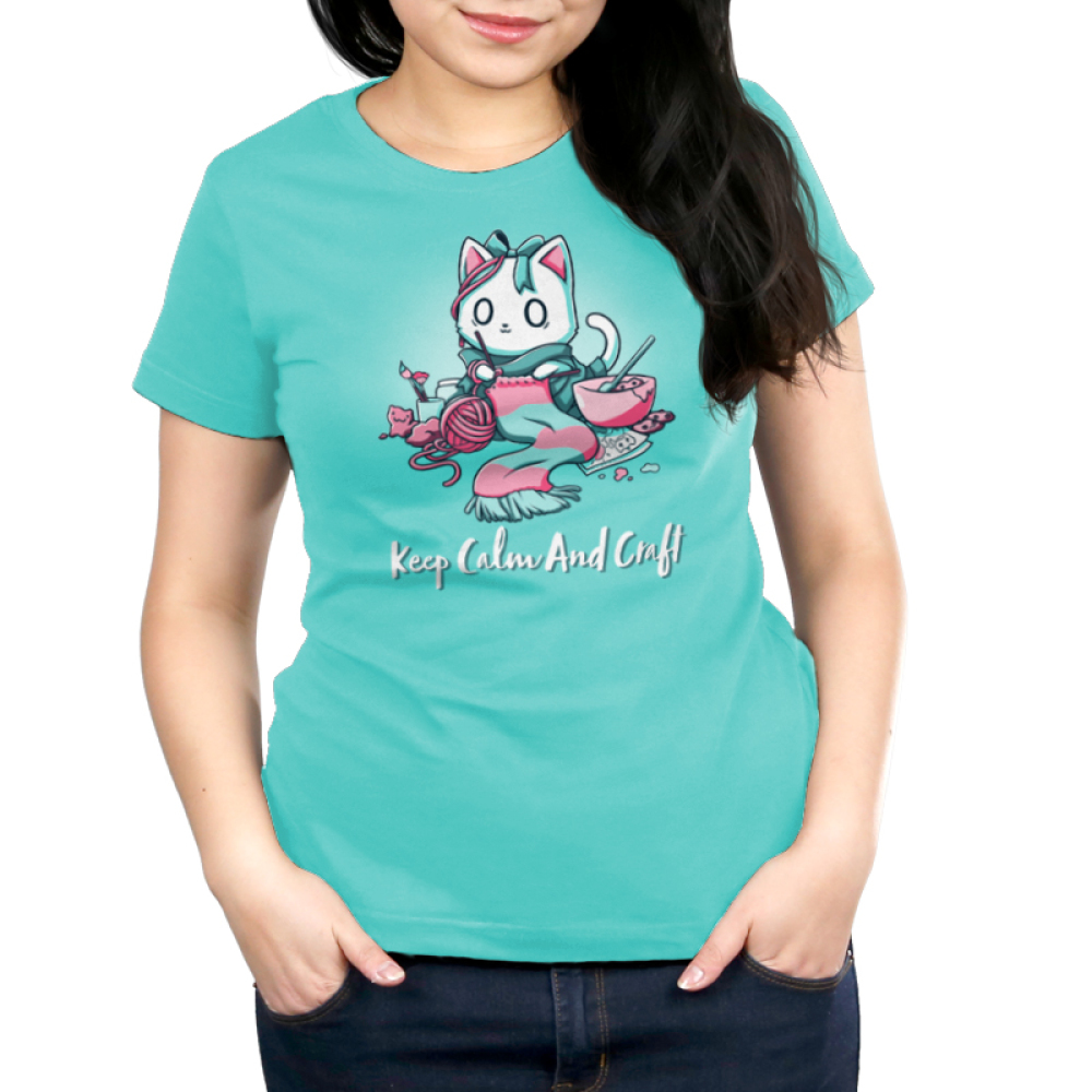 Keep Calm and Craft Women's t-shirt model TeeTurtle Caribbean blue t-shirt featuring an anxious white cat wearing a green bow while knitting a green and pink scarf while surrounded by drawing, baking, sculpting, and painting materials.