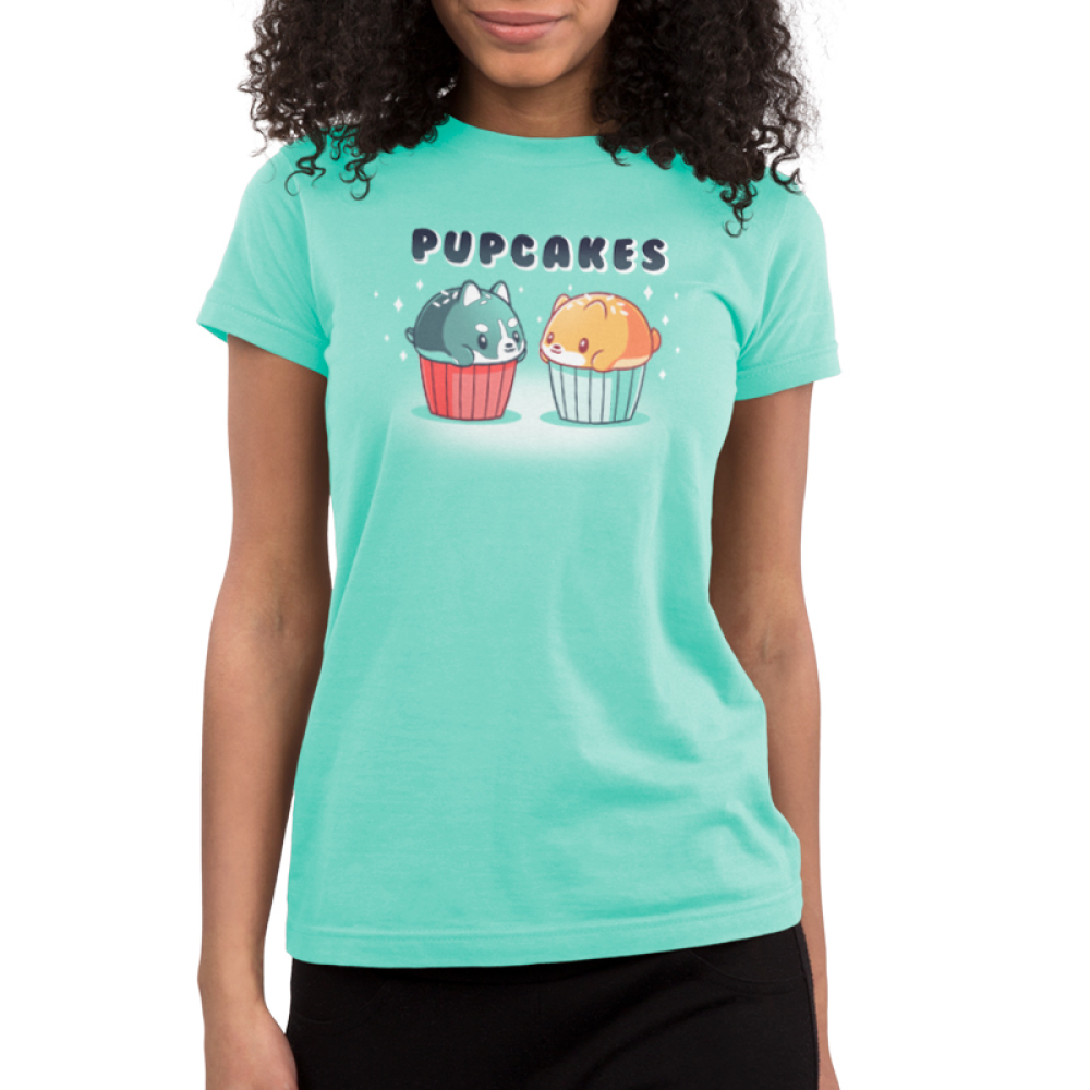 Pupcakes Junior's t-shirt model TeeTurtle chill blue t-shirt featuring a husky puppy in the shape of a cupcake with white sprinkles with a red wrapper on the left-hand side, and a corgi puppy in the shape of a cupcake with white sprinkles and a chill blue wrapper on the right-hand side with a sparkly background.