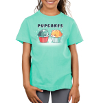 Pupcakes Kid's t-shirt model TeeTurtle chill blue t-shirt featuring a husky puppy in the shape of a cupcake with white sprinkles with a red wrapper on the left-hand side, and a corgi puppy in the shape of a cupcake with white sprinkles and a chill blue wrapper on the right-hand side with a sparkly background.