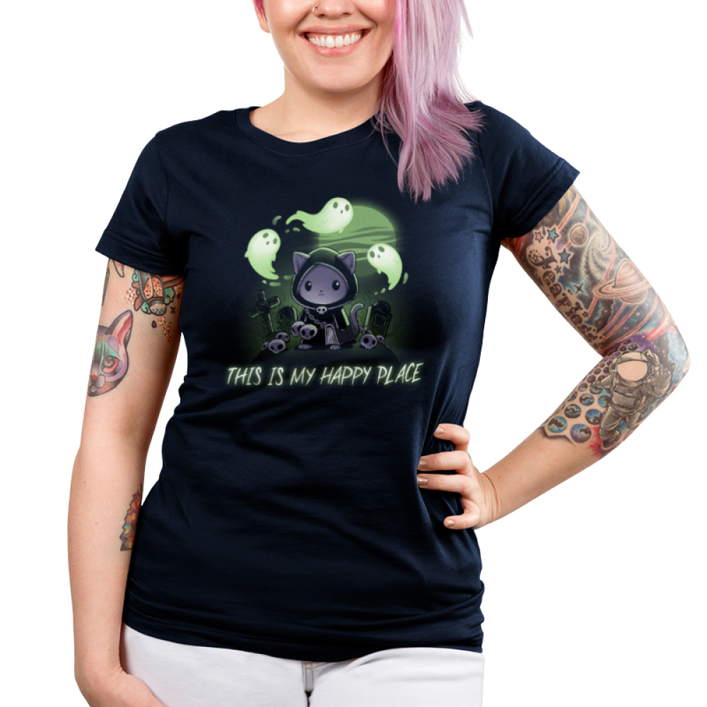 Graveyards are My Happy Place Junior's t-shirt model TeeTurtle navy t-shirt featuring a cat in a cloak with a chain around its chest holding a big hook with skulls around him, grave stones in the background, a full moon, and ghosts flying around