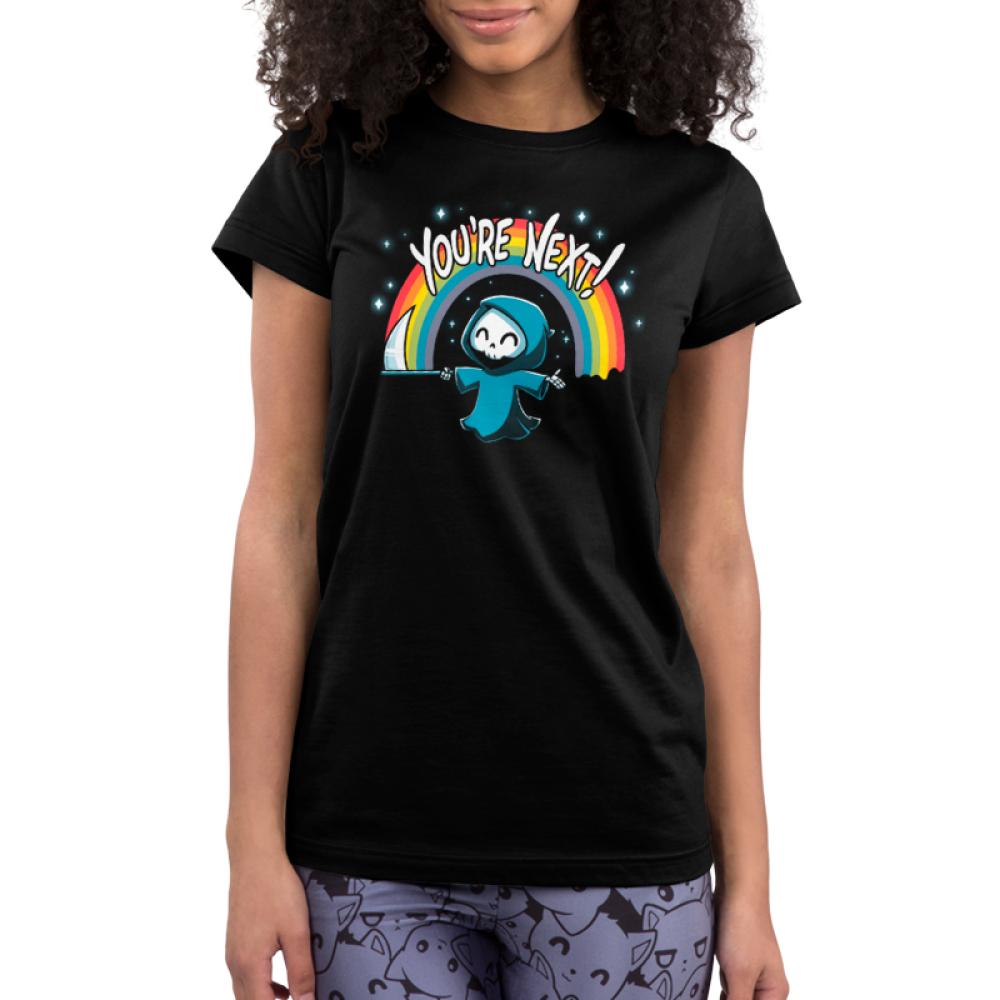 You're Next Junior's t-shirt model TeeTurtle black t-shirt featuring a smiling grim reaper in his cloak holding out his scythe with a rainbow and sparkles behind him