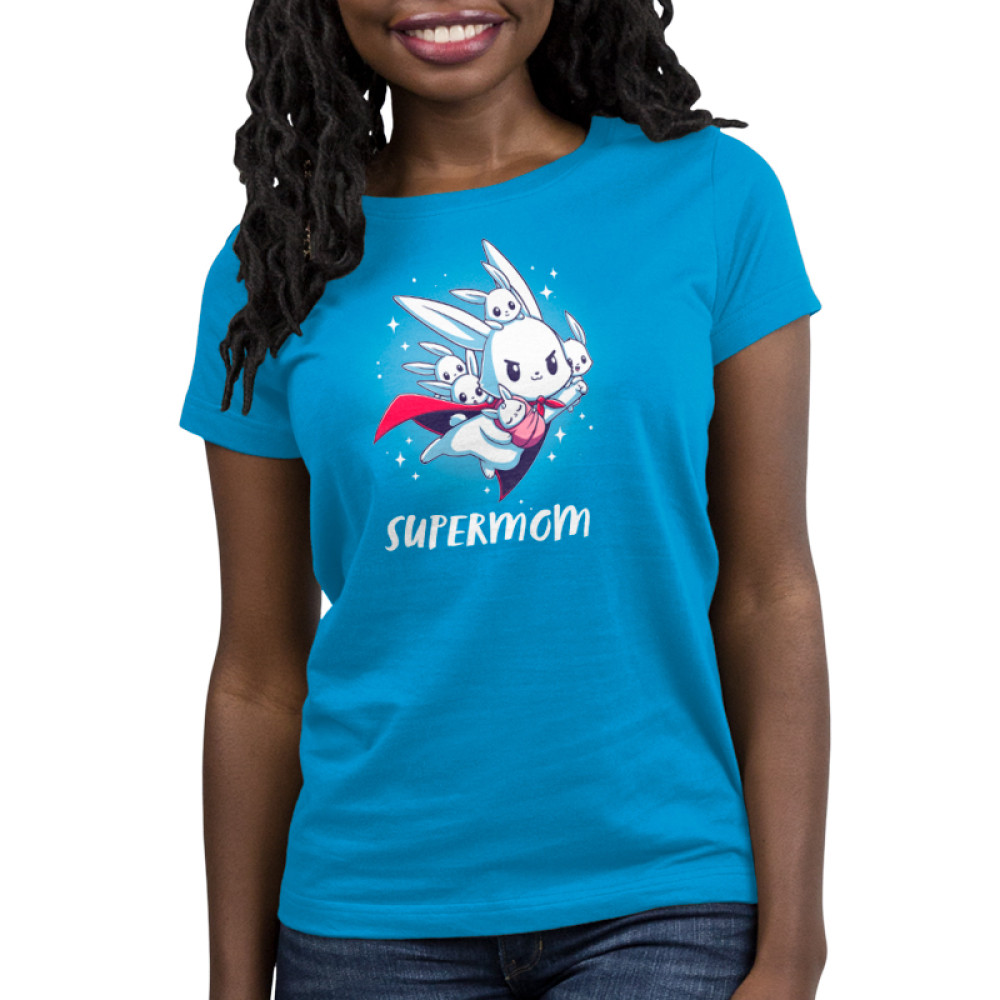 Supermom Women t-shirt model TeeTurtle cobalt blue t-shirt featuring a mama bunny with a cap flying with a little wrapped baby bunny in her arms and four other little bunnies on her back