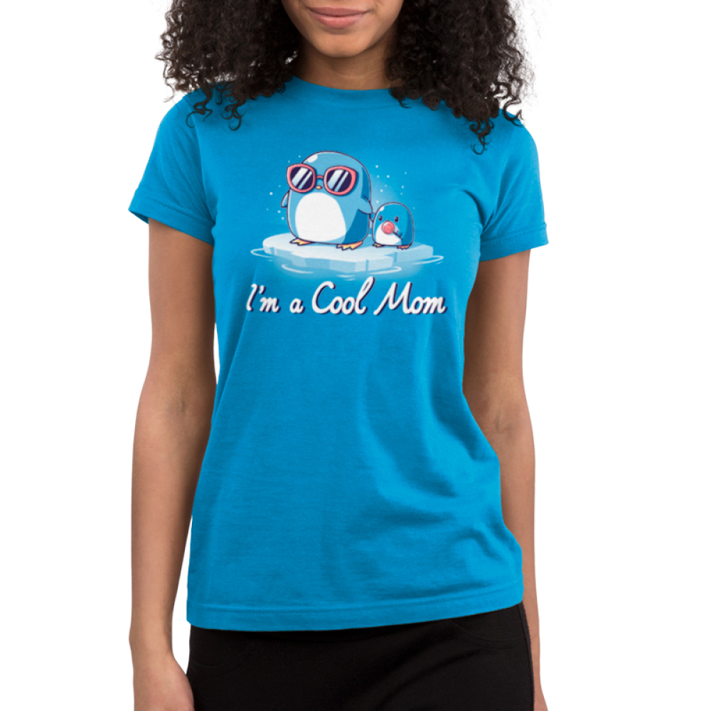 I'm a Cool Mom Juniors t-shirt model TeeTurtle cobalt blue t-shirt featuring a mama penguin in pink sunglasses on a floating ice burg holding the hand of a baby penguin holding a lolly pop