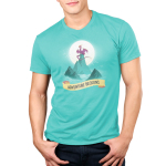 Adventure Beckons Men's t-shirt model TeeTurtle Caribbean blue t-shirt featuring blue mountains in the middle of wavy water with a big purple dragon sitting on the highest peak with a big sun behind him and birds flying
