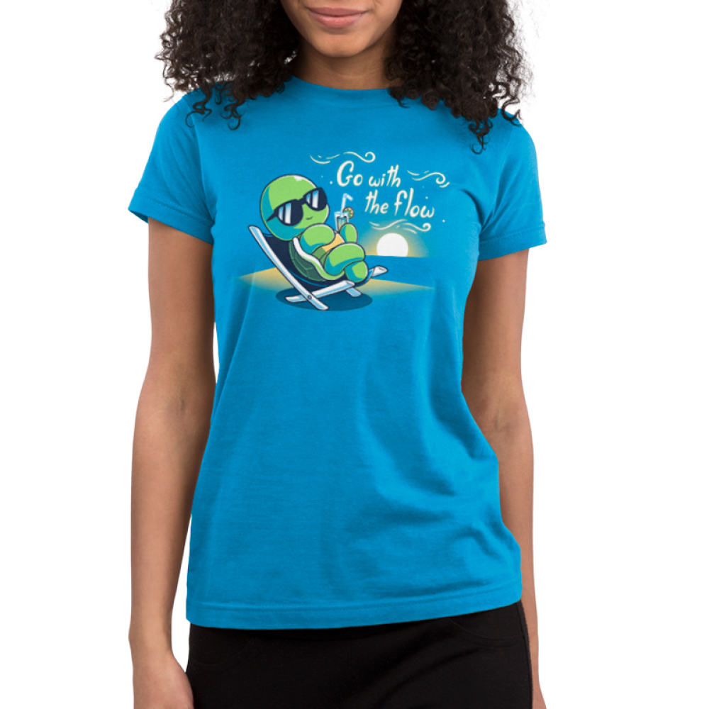 Go With the Flow Junior's t-shirt model TeeTurtle cobalt blue t-shirt featuring a turtle in an outdoor lounge chair with sunglasses on sipping a lemonade with a sun setting behind him