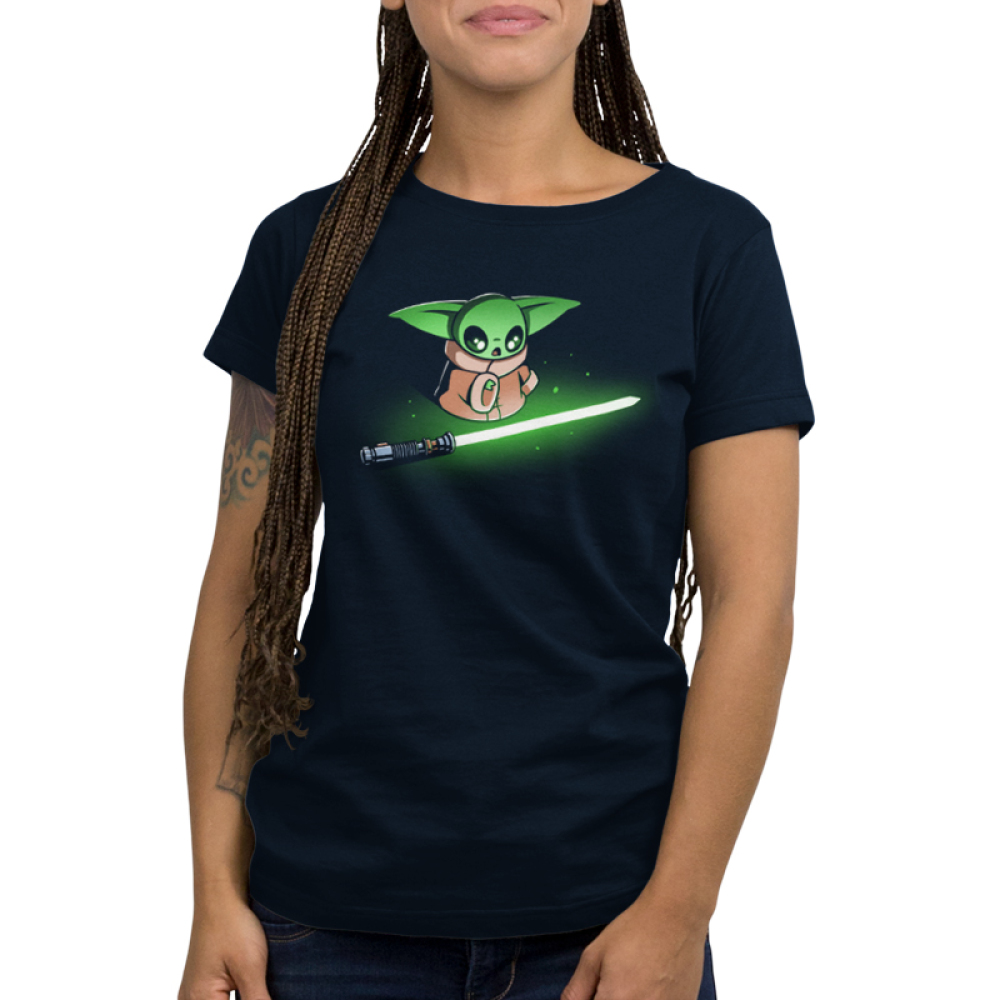 Shiny Lightsaber womens tshirt model officially licensed black tshirt featuring grogu looking at a bright green lightsaber