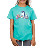 Baking Unicorn Kid's t-shirt model TeeTurtle Caribbean blue t-shirt featuring a white unicorn with a purple mane mixing batter in a bowl with ingredients all around him including rainbows, magic, and glitter