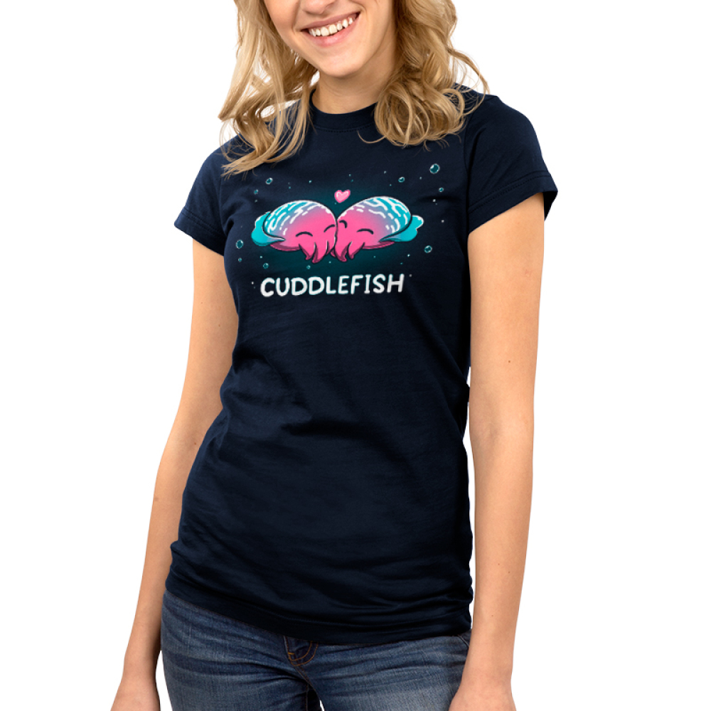 Cuddlefish Junior's t-shirt model TeeTurtle navy t-shirt featuring two pink, blue, and white, cuttle fish snuggling up against each other with a heart between them and bubbles around them