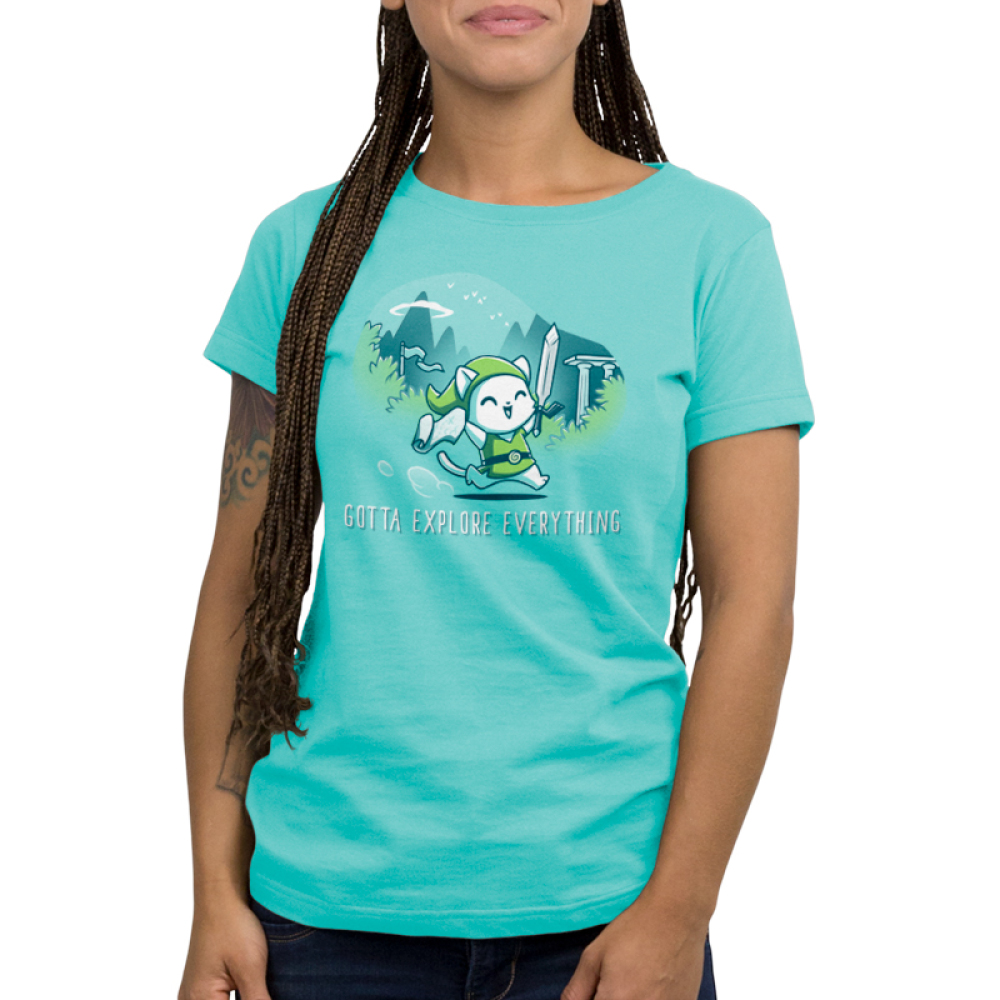 Gotta Explore Everything Women's t-shirt model TeeTurtle caribbean blue t-shirt featuring a white cat in a green floppy cap and green vest holding a sword and a scroll running with mountains, trees, and birds behind him