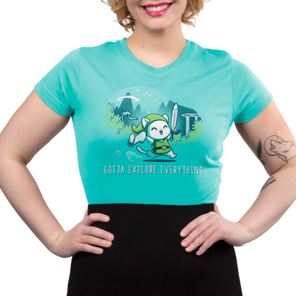 Gotta Explore Everything Junior's t-shirt model TeeTurtle caribbean blue t-shirt featuring a white cat in a green floppy cap and green vest holding a sword and a scroll running with mountains, trees, and birds behind him