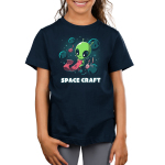 Space Craft Kid's t-shirt model TeeTurtle navy t-shirt featuring a green alien gloating in space with big eyes looking down at a pink scarf they are knitting with crafting supplies floating around them as well as planets and stars in the background