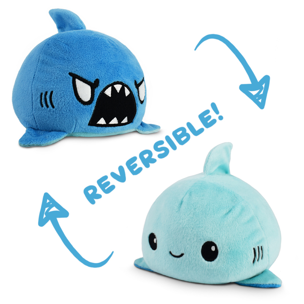 An angry blue reversible shark plushie flipping to a happy light blue reversible shark plushie.