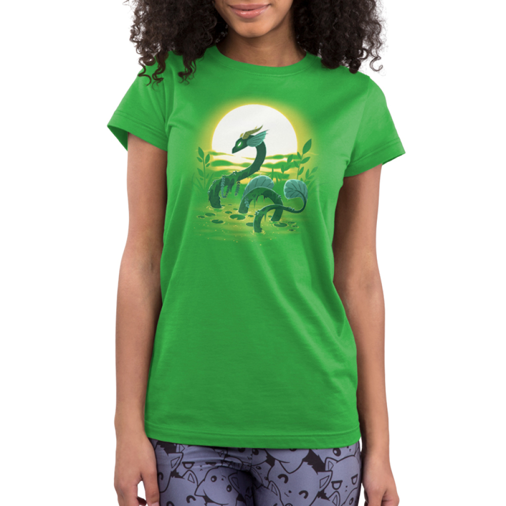 Swamp Dragon Junior's t-shirt model TeeTurtle apple green t-shirt featuring a dark green dragon coming out of a green swamp with miss and leaves draping over its body with a sun and plants behind him