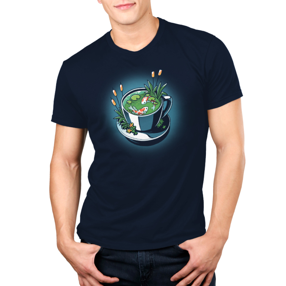 Cup of Koi Men's t-shirt model TeeTurtle navy t-shirt featuring a white tea cup with two orange and white koi fish swimming in it with lily pads and plants in the tea cup with the fish and on the plate the tea cup is on