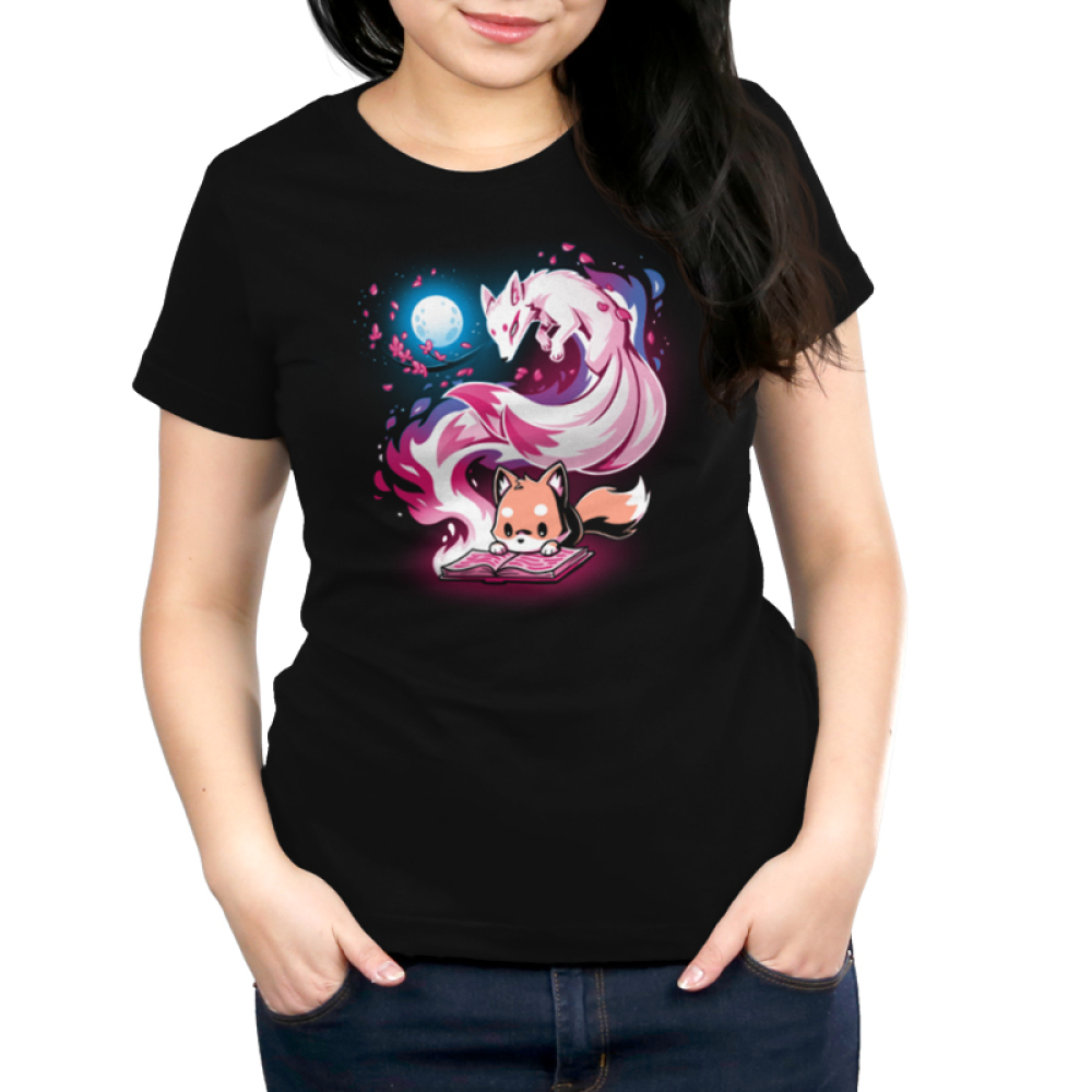 Tale of Tails Women's t-shirt model TeeTurtle black t-shirt featuring a little orange fox hunched over reaching a book on the ground with a big swirly pink kitsune coming out of the book with branches with pink leaves by the kitsune and a white full behind them