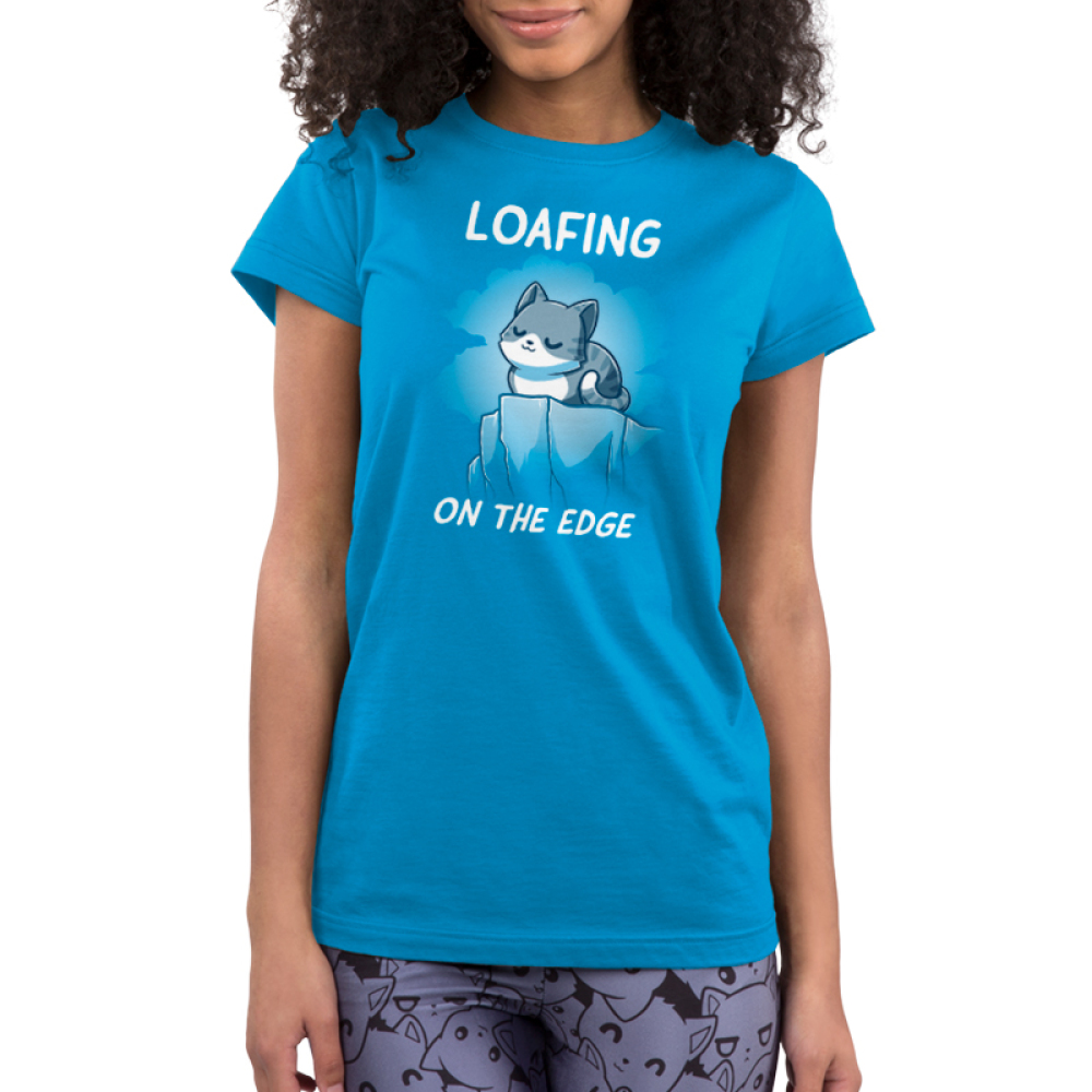 Loafing on the edge cobalt blue juniors  tshirt model  featuring a cat curled up on the edge of a cliff