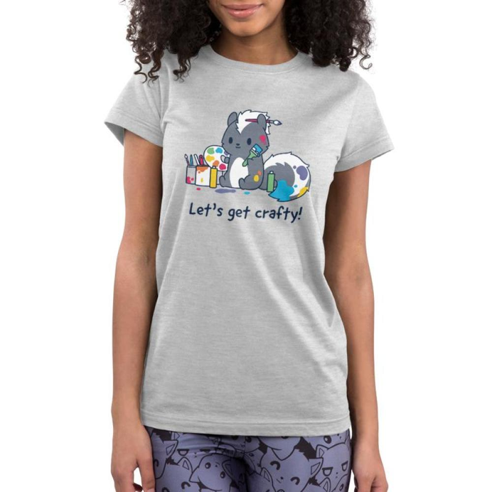 Let's Get Crafty! Juniors T-Shirt Model TeeTurtle Gray t-shirt featuring a skunk covered in paint and holding a paint brush and a palette while surrounded by paint cans with shirt text reading