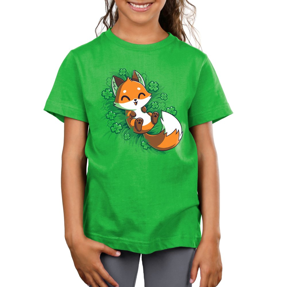 Lucky Fox Kid's T-shirt model TeeTurtle green t-shirt featuring an orange fox lying in a field of four leaf clovers