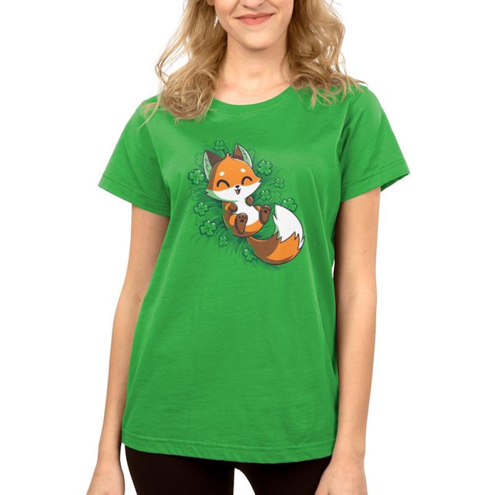 Lucky Fox Women's T-shirt model TeeTurtle green t-shirt featuring an orange fox lying in a field of four leaf clovers