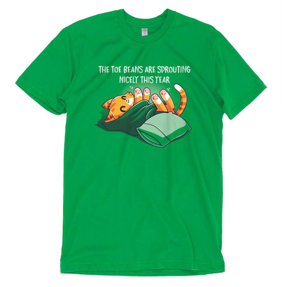 Toe Beans T-shirt TeeTurtle green t-shirt featuring an orange cat wrapped up in a green blanket with a pillow next to him and shirt text